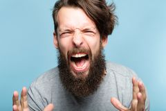 Anger fury emotional breakdown enraged man scream. Anger and fury. emotional breakdown. enraged man screaming. portrait of a young bearded guy on blue background royalty free stock images