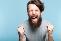 Anger fury emotional mental breakdown man scream. Anger and fury. emotional or mental breakdown. enraged man screaming. portrait of a young bearded guy on blue stock photos