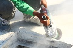 Anger grinder. Worker use angle grinder to cut concrete Stock Image
