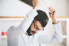 Anger issues and stress concept. Furious man at workplace throwning his laptop. Anger issues and stress concept stock image