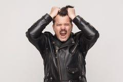 Anger man scream at camera and holding head. Studio shot Stock Photo
