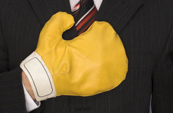 Anger management. Photo showing a businessman wearing boxing glove Royalty Free Stock Image