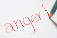 Anger. A red pencil hits a piece of paper with the word 'anger' written on it royalty free stock photos