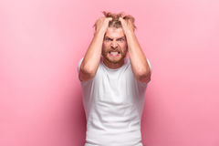 The anger and screaming man. At pink studio background stock photo
