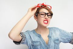 Anger sexual young woman in casual blue denim shirt with makeup standing, wearing lots of colorful spectacles at the same time,. Clench one`s teeth . indoor royalty free stock images