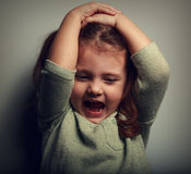 Anger shouting kid holding head with open mouth. Closeup Royalty Free Stock Images