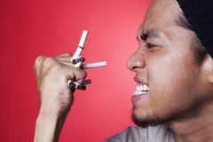 Anger smoker. Anger asian smoker crushing the cigarettes isolated on red Stock Photo