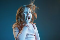 The anger and surprised teen girl. Hate, rage. Crying emotional angry teenager in colorful bright lights at studio background. Emotional face. Sport fan human Royalty Free Stock Photos
