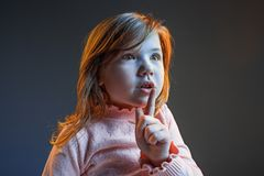 The anger and surprised teen girl. Hate, rage. Crying emotional angry teenager in colorful bright lights at studio background. Emotional face. Sport fan human Royalty Free Stock Photography