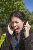 Anger woman shouting two phones. Anger woman shouting with two mobiles in exterior Royalty Free Stock Photography