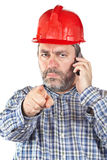 Angered construction worker. With hardhat while talking with phone isolated on a white background. Eyes on focus Royalty Free Stock Image