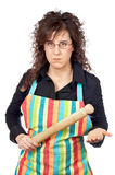 Angered housewife. In apron holding a wooden rolling Royalty Free Stock Photography