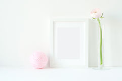 Angeredetes Modell mit weißem Rahmen und rosa ranunculos Stockfoto