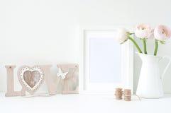 Angeredetes Modell mit weißem Rahmen und rosa ranunculos Lizenzfreies Stockfoto