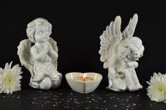 Anges de Noël avec des fleurs pour des cadeaux, d'isolement sur le noir Image stock