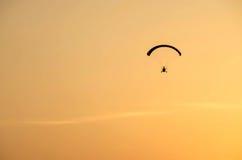 Angeschaltenes Gleitschirmflugwesen weg mit Sonnenaufgang stockbild