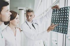 Angespannter männlicher Doktor Indicates auf Bild des Röntgens lizenzfreie stockbilder