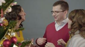 Angespornt durch die Feierstimmungsfamilie, die zusammen Weihnachtsbaum zu Hause verziert stock video