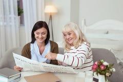 Angespornte älteren Untersuchungszeitung der Frau und der Pflegekraft lizenzfreie stockfotos