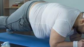 Angespornte übende Plankenübung des überladenen Sportlers auf Matte, Fitness-Programm stock video footage