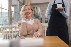 Angespornte Frau, die auf ihren Kaffee wartet Lizenzfreie Stockfotos