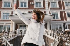 Angespornte Frau, die am sonnigen Wintertag, Weihnachtsfeiertage genießend springt Foto im Freien des lustigen weiblichen Modells lizenzfreies stockfoto