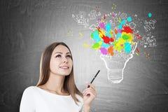 Angespornte Frau mit Stift und bunter Glühlampe Stockbilder
