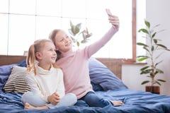 Angespornte Schwestern, die Fotos an ihrem Telefon machen Stockbilder