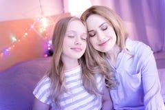 Angespornte umarmende und träumende Mutter und Tochter Lizenzfreies Stockfoto