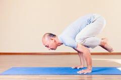 Angespornter asiatischer Mann, der die Übung von Yoga Innen tut Stockfotografie