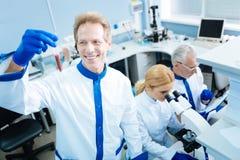Angespornter Forscher, der das Reagenzglas betrachtet Lizenzfreies Stockfoto