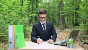 Angespornter Geschäftsmann, der seine Ideen in das Notizbuch, sitzend am Schreibtisch im Wald schreibt stock video footage