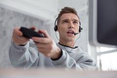 Angespornter Jugendlicher, der ein Computerspiel spielt Stockfoto