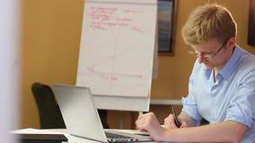 Angespornter junger Geschäftsmann in der blauen Hemdfunktion, Glaslaptop stock footage