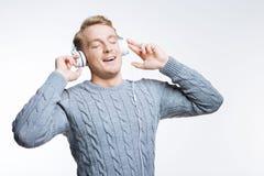 Angespornter junger Mann, der Musik in den Kopfhörern genießt Lizenzfreies Stockfoto