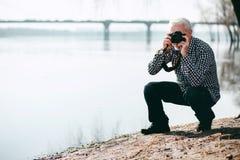 Angespornter reifer Mann, der Bilder schafft stockfoto