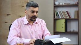 Angespornter Romanautor, der das folgende Kapitel des Bestsellerbuches, trinkender Kognak schreibt stock video footage