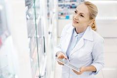 Angespornter weiblicher Apotheker, der Medikation überprüft stockbild