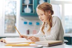 Angesporntes Schulmädchen, das ein Buch am Tisch liest Stockbilder