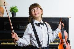 Angesporntes und glückliches Mädchen, das eine Violine Innen hält Stockfotos