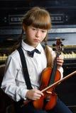Angesporntes und glückliches Mädchen, das eine Violine Innen hält Lizenzfreie Stockfotografie