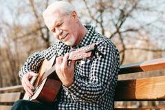 Angesporntes versuchendes Gitarrenspiel des reifen Mannes lizenzfreie stockfotografie