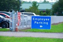 Angestellt-Parkzeichen mit Pfeil und parkendes Auto hinter Zaun Lizenzfreies Stockfoto