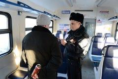 Angestellte der Transportpolizei fingen den Passagier mit einem Bier im Zug Lizenzfreie Stockfotografie
