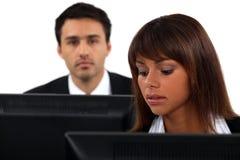 Angestellte, die durch ihre Computer sitzen Stockfoto