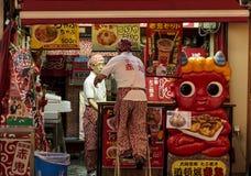 Angestellte, die eine Straßenstange in Dotombori, Osaka, Japan schließen Stockfotografie