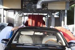 Angestellte, die Fahrzeug in der Waschanlage abwischen Stockfotos