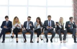 Angestellte mit den Smartphones, die in der Lobby sitzen Lizenzfreies Stockfoto