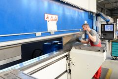 Angestellter betreibt verbiegende Maschine in einer Metallarbeitsfirma - Verbiegen des Blechs für die Weiterverarbeitung stockfoto