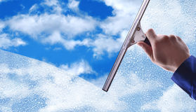 Angestellter, der ein Glas mit Regentropfen und blauem Himmel säubert Lizenzfreies Stockfoto